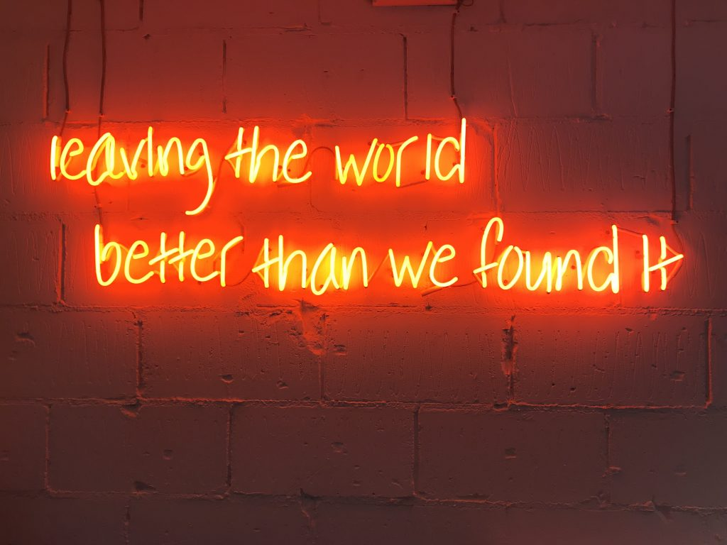 Neon sign reads leaving the world better than we found it